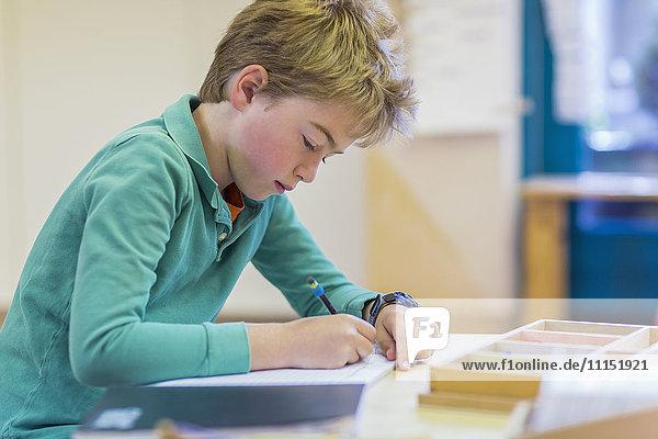 Caucasian boy writing in classroom