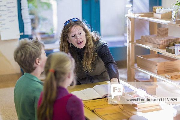 Caucasian Montessori teacher helping students in classroom
