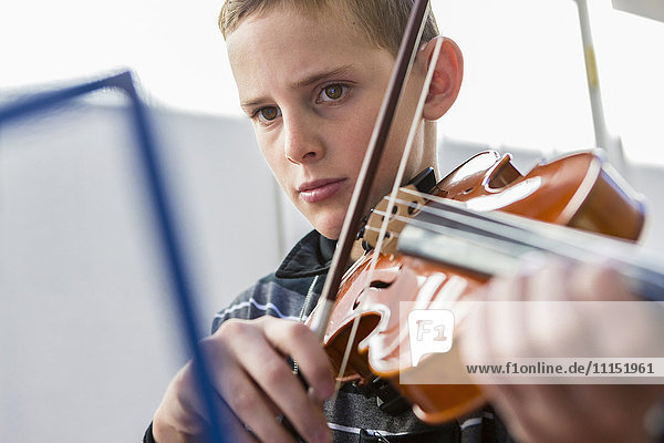 Close up of Caucasian boy playing violin