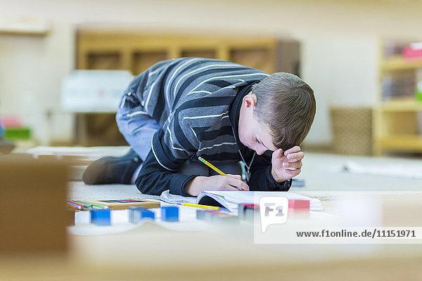 Caucasian boy writing in notebook on floor in classroom