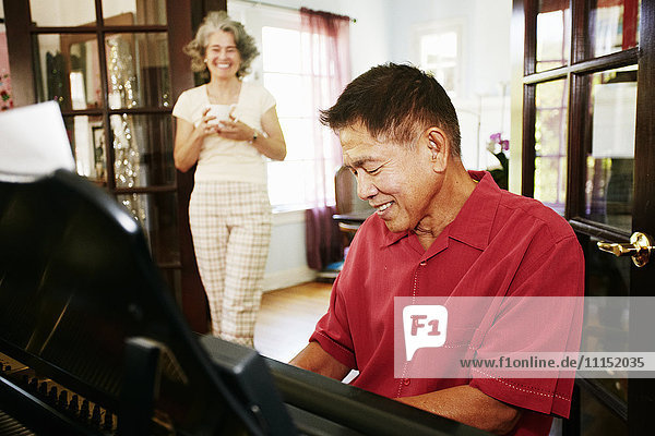Woman watching husband playing piano in living room