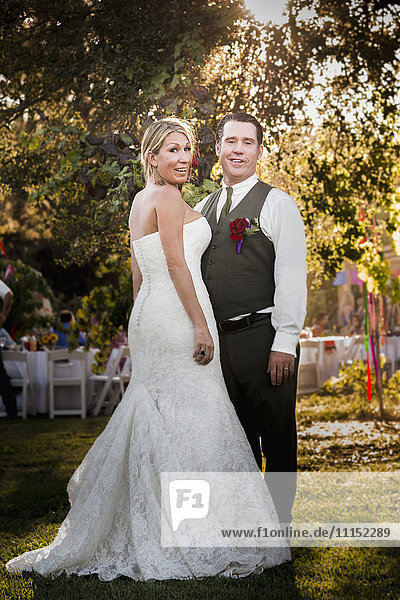 Caucasian bride and groom smiling at outdoor reception