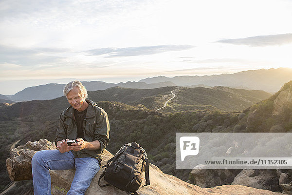 Older Caucasian man using cell phone on rocky hilltop