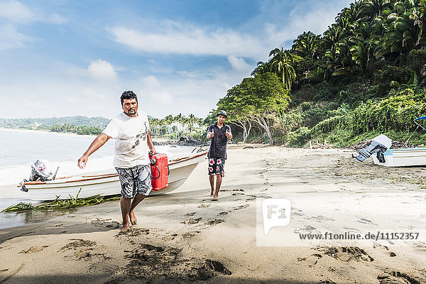 Man carrying fuel can from boat to beach