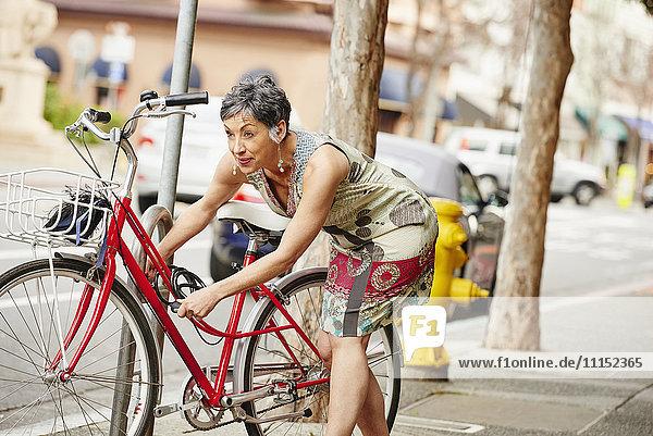 Older Caucasian woman locking bicycle to rack on city sidewalk