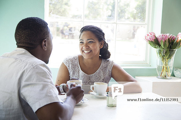 Smiling couple drinking coffee at table