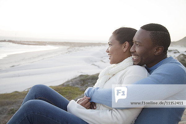 Couple hugging on cliffs over beach