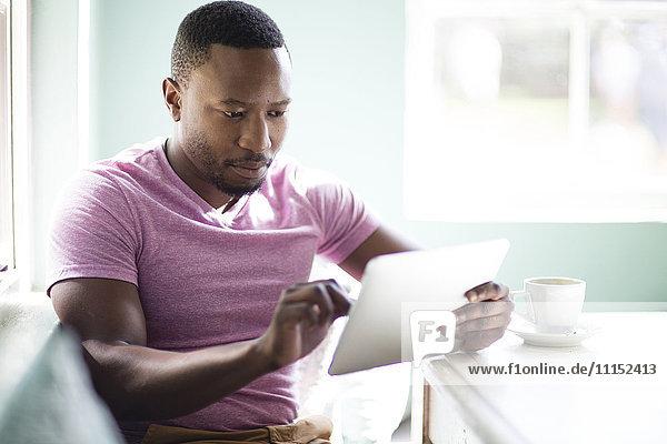 Black man using digital tablet at breakfast
