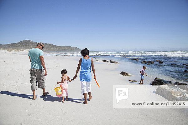 Mixed race family walking on beach