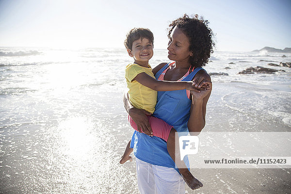 Mixed race mother carrying daughter on beach