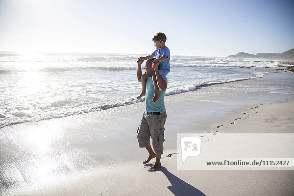 Mixed race father carrying son on shoulders on beach