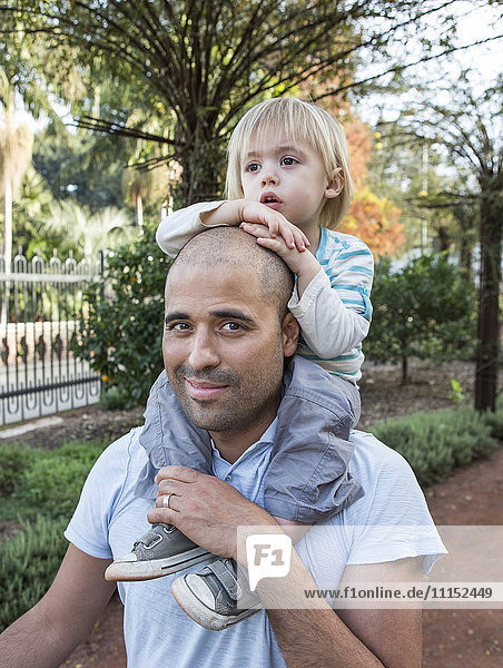 Hispanic father carrying son on shoulders in park