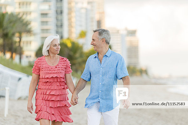 Older Caucasian couple walking on beach