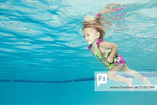 Underwater view of Caucasian girl swimming in pool