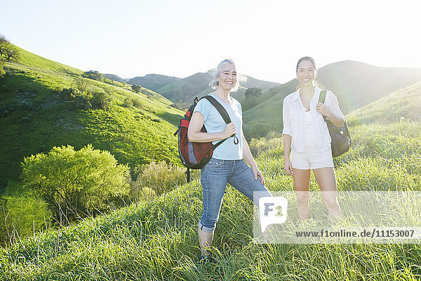 Caucasian mother and daughter smiling on grassy hillside