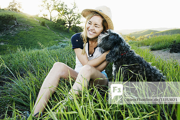Caucasian woman petting dog in field Caucasian woman petting dog in field