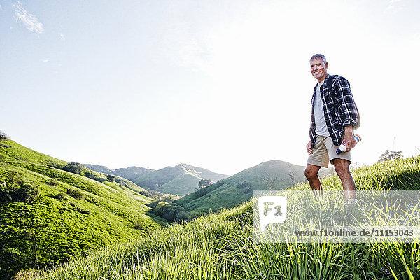 Older Caucasian man smiling on grassy hillside Older Caucasian man smiling on grassy hillside