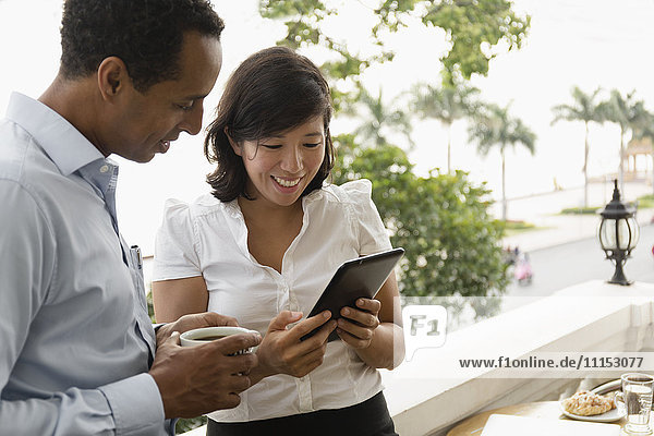 Business people using digital tablet on balcony