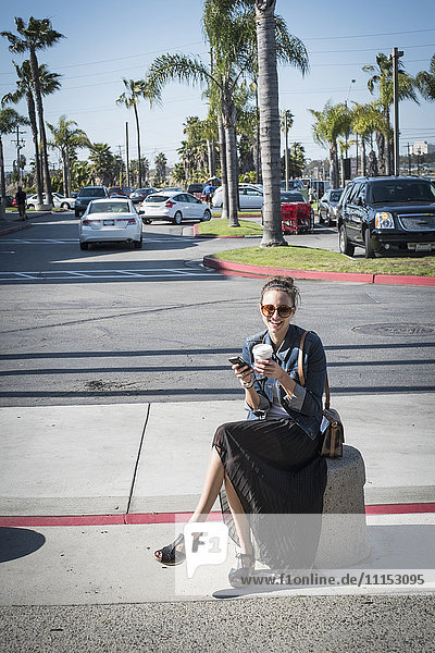 Caucasian woman sitting on concrete barrier in parking lot