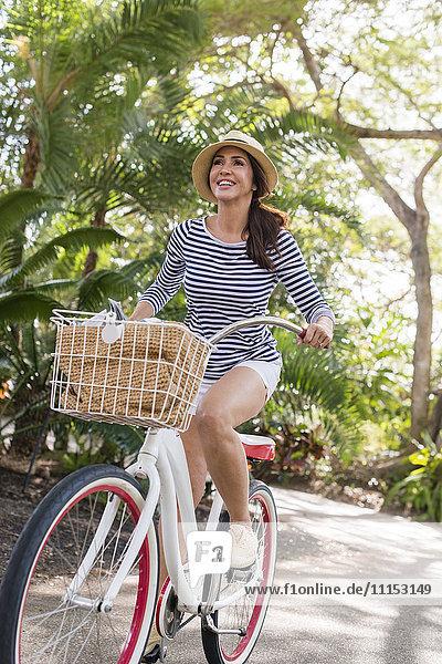 Hispanic woman riding bicycle on path
