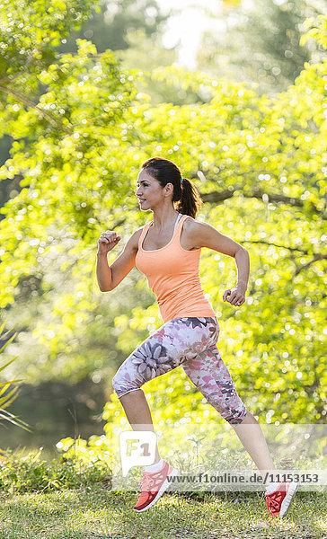 Hispanic woman jogging in park
