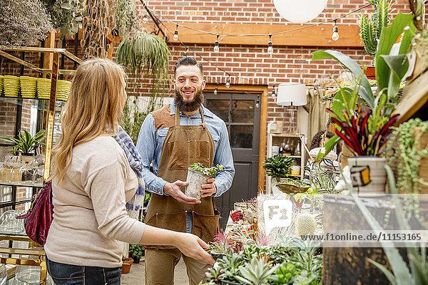 Caucasian employee helping customer in plant nursery