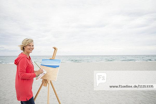 Older Caucasian woman painting on beach