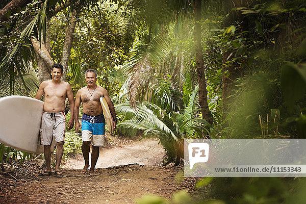 Hispanic men carrying surfboards on jungle trail