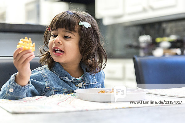 Girl eating waffle fries in kitchen
