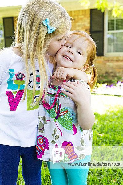 Caucasian sisters kissing in backyard