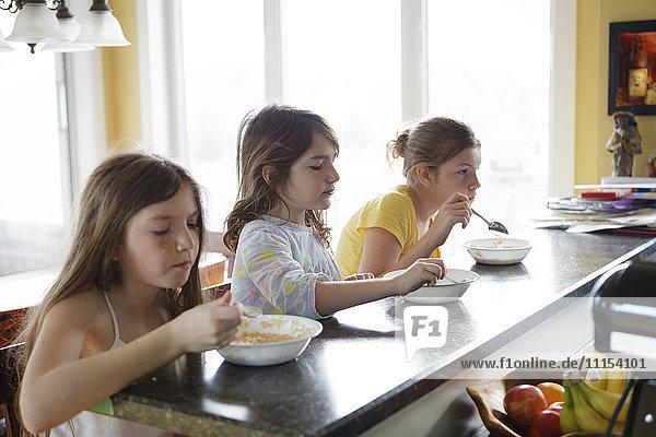 Caucasian sisters eating breakfast in kitchen