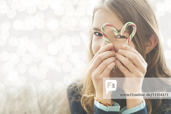 Caucasian girl looking through heart-shape with candy canes