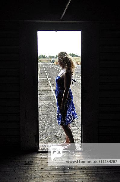 Woman standing in doorway of train in train yard