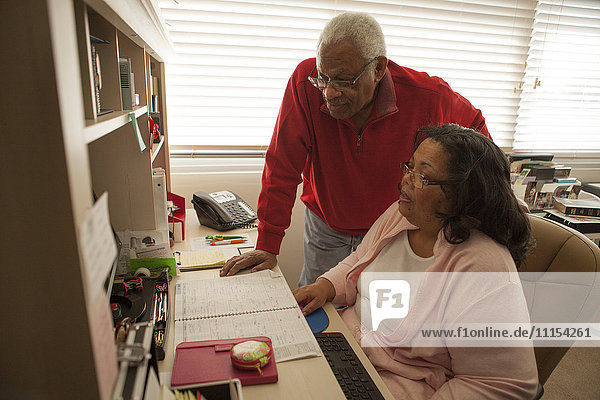Couple using computer in home office