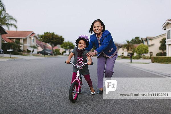 Grandmother teaching granddaughter to ride bicycle on suburban street