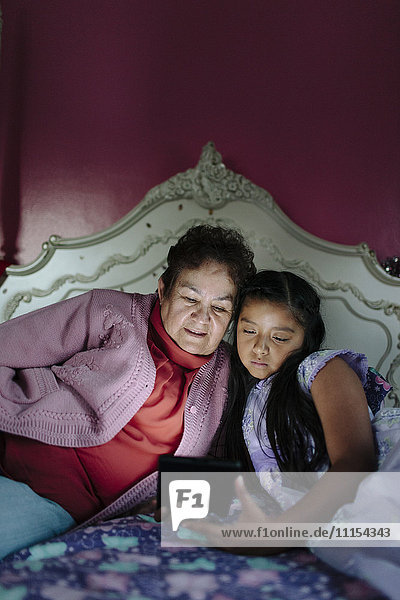 Hispanic grandmother and granddaughter using digital tablet on bed