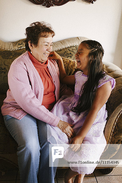 Hispanic grandmother and granddaughter laughing on sofa