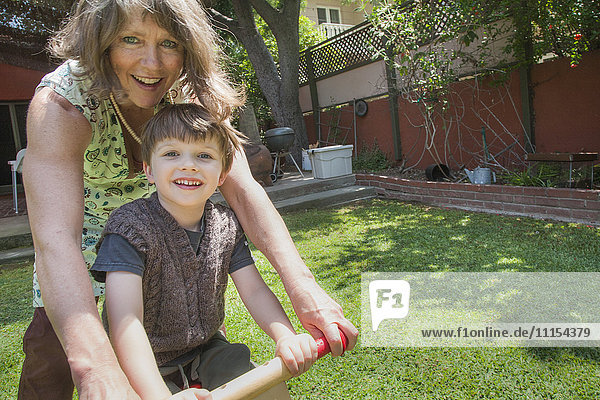 Caucasian grandmother and grandson riding bicycle in backyard
