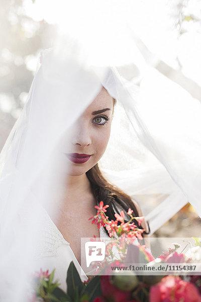 Caucasian bride holding bouquet under veil