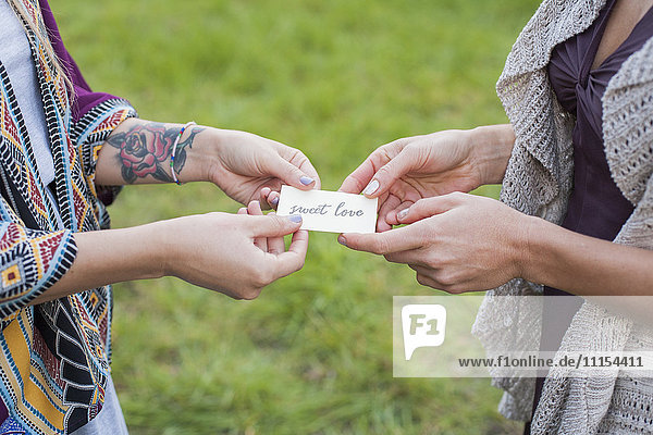 Close up of friends holding sweet love card