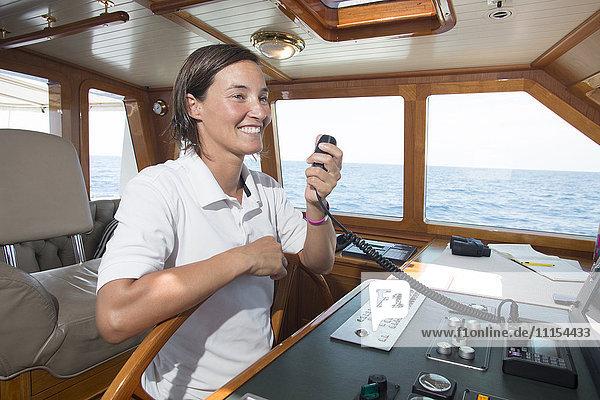 Caucasian woman steering boat and using radio