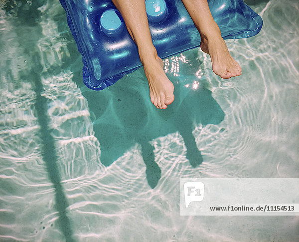 Feet of Caucasian woman floating on raft in swimming pool