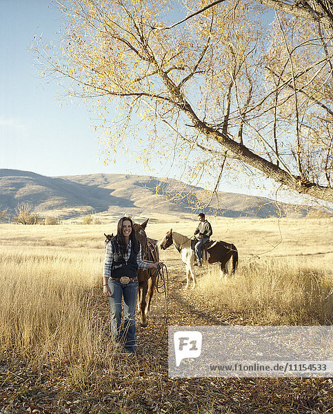 Couple leading horses on dirt path