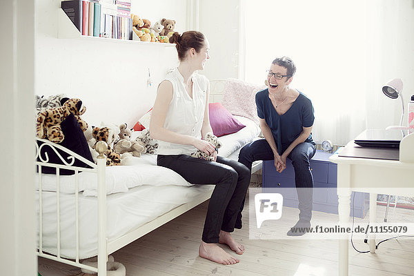 Caucasian mother and daughter talking in bedroom