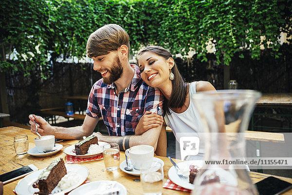 Ein glückliches junges Paar sitzt draußen bei Kaffee und Kuchen.