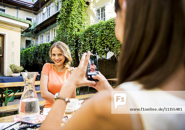 Junge Frau macht Handyfoto von Freundin im Outdoor-Café