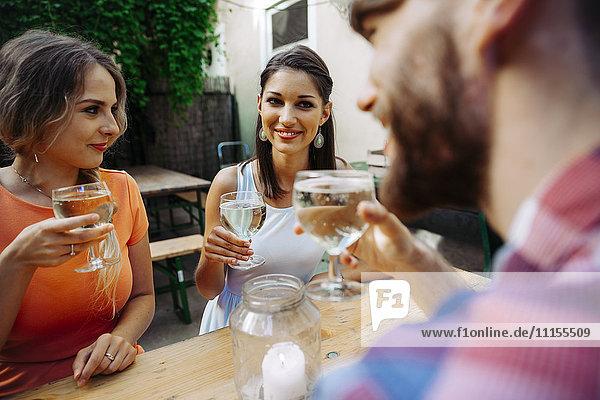 Freunde trinken Schorle in der Außenkneipe