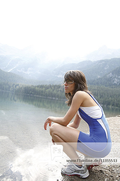 Caucasian woman crouching near remote lake