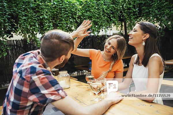 Fröhliche Freunde trinken Schorle in einem Pub im Freien