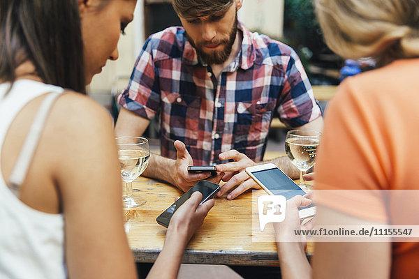 Freunde  die Mobiltelefone benutzen und Schorle trinken in einem Pub im Freien